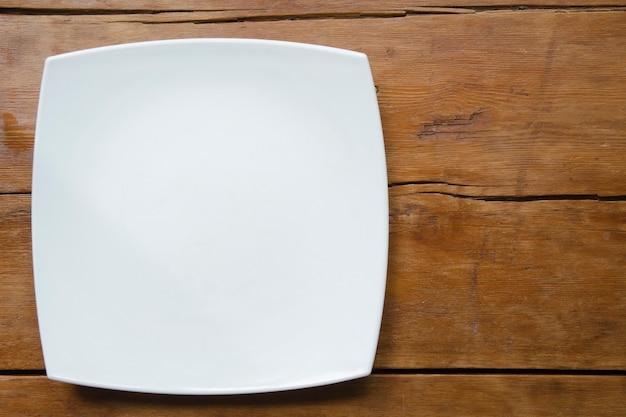 Plato cuadrado de cerámica blanca sobre la mesa de madera vintage