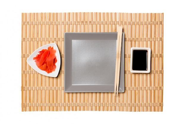 Plato cuadrado gris vacío con palillos para sushi