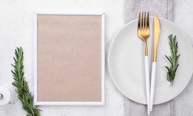 Plato con cubiertos y marco sobre mesa