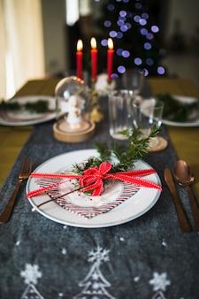Plato con cubiertos sobre mesa decorada para navidad.