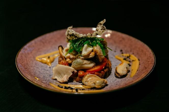Plato de ensalada de mariscos con salsa. presentación moderna comida del restaurante