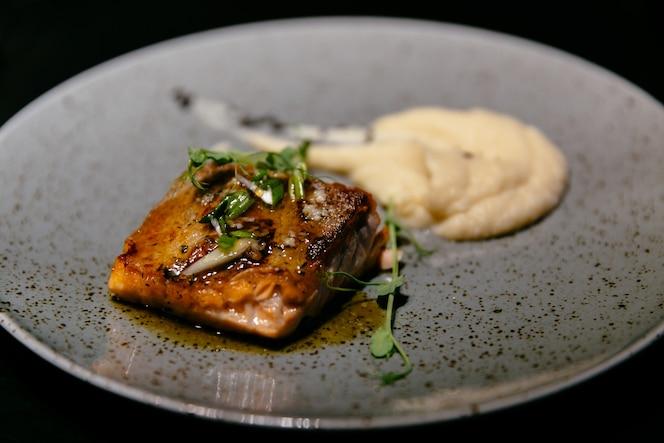 Plato de sabroso filete de salmón con salsa y puré en restaurante de comida moderna.