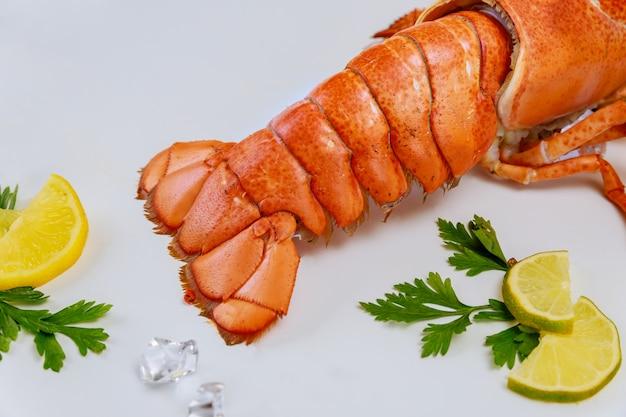 Plato delicioso cangrejo cola con limón sobre fondo blanco.