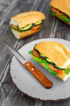 Plato con delicioso sándwich y cuchillo