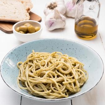 Plato con deliciosos espaguetis en el escritorio