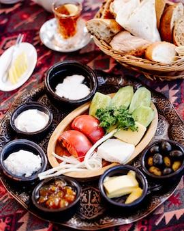 Plato de desayuno con alimentos mezclados, pan y un vaso de té.
