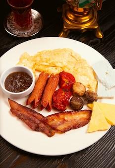 Plato de desayuno con crepé, mermelada, salchichas fritas, tocino, tomates cherry y variaciones de queso.