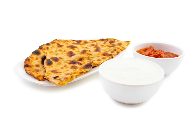 Plato de desayuno indio aloo paratha servido con cuajada y pepinillo