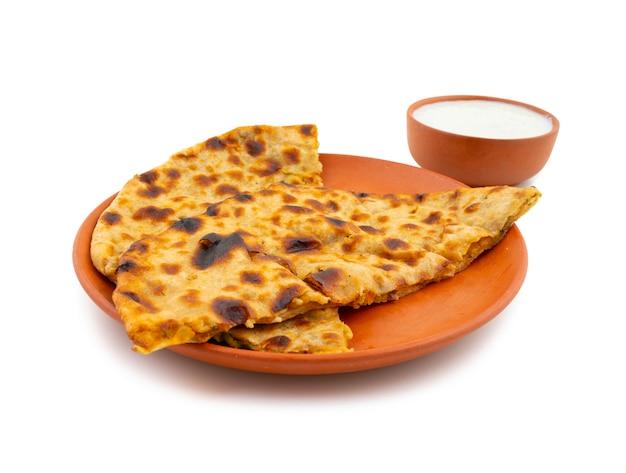 Plato de desayuno indio aloo paratha servido con cuajada sobre fondo blanco.