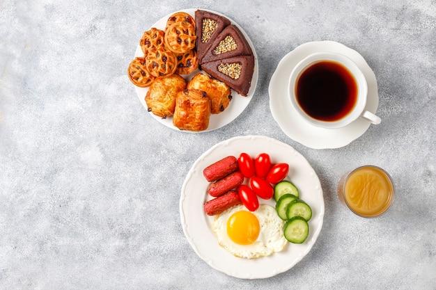 Un plato de desayuno que contiene salchichas tipo cóctel, huevos fritos, tomates cherry, dulces, frutas y un vaso de jugo de durazno.