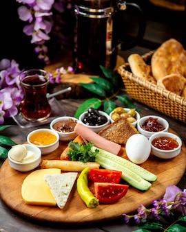 Plato de desayuno turco con queso, verduras, aceitunas, mermeladas, salchichas y envoltura de pan plano