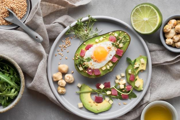 Plato de dieta keto: bote de aguacate al horno con cubos de jamón, huevo de codorniz y queso servido con ensalada verde