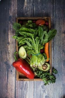 Un plato con diferentes verduras de temporada colocadas en medio de una mesa de madera oscura.