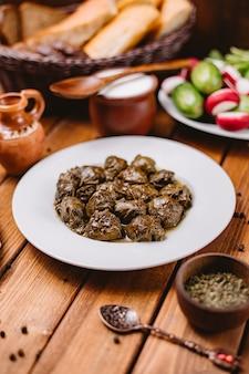 Plato dolma de hojas de uva azerbaiyana servido con yogur y ensalada