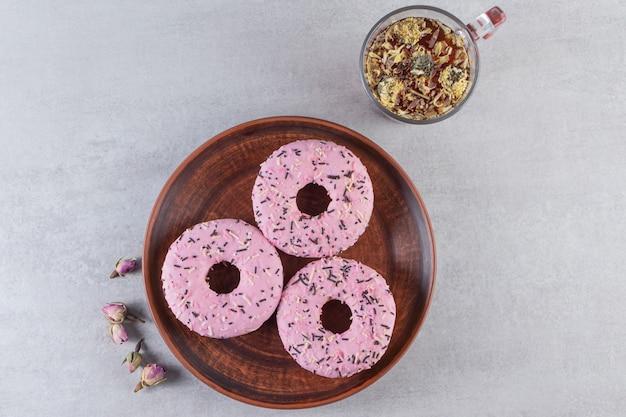 Plato de donas rosas dulces con taza de té caliente sobre la superficie de piedra.