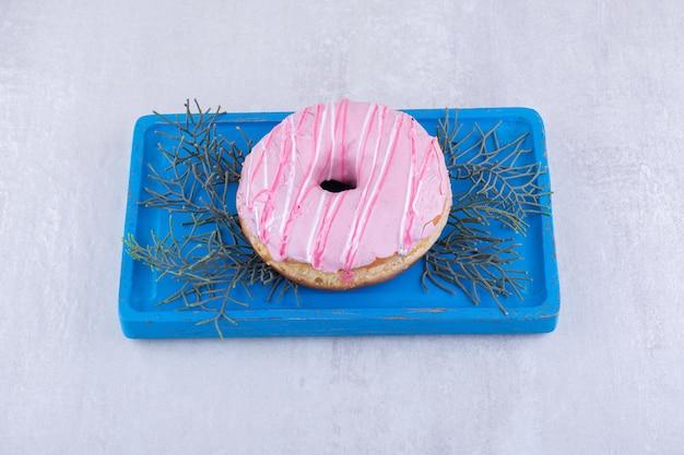 Plato con un donut glaseado colocado sobre hojas de pino sobre superficie blanca