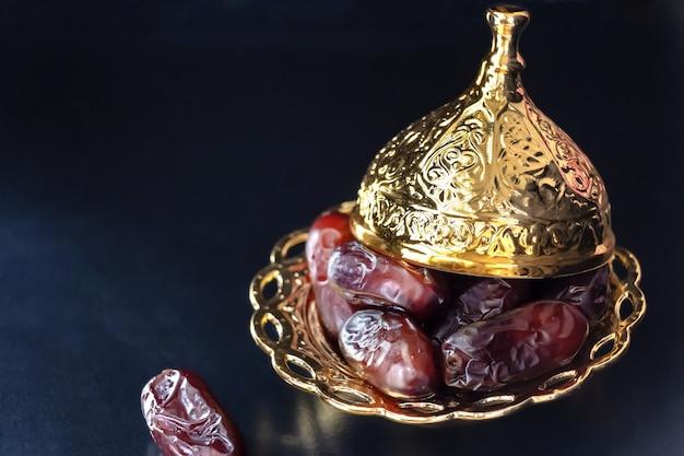 Plato dorado con frutos de palmera datilera o kurma. concepto de ramadan kareem.