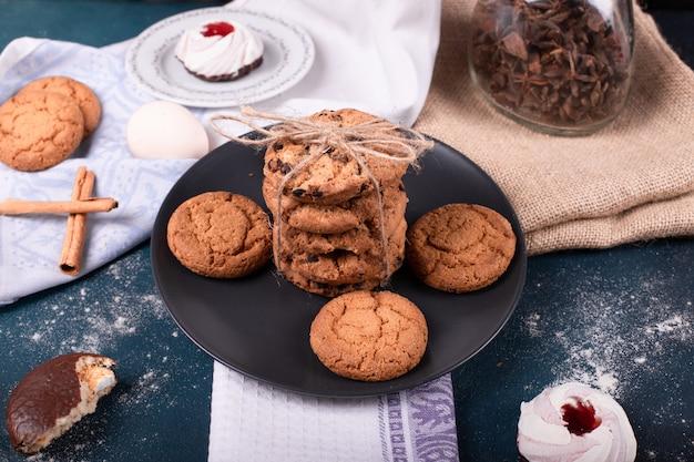 Plato de dulces y dos pasteles y galletas con canela