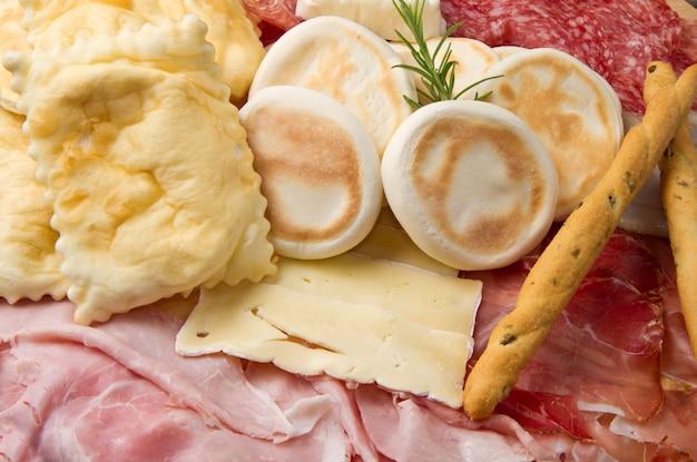 Plato de embutidos, quesos y bola de masa frita.
