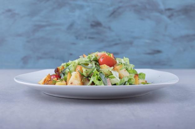 Plato de ensalada fresca con salchichas sobre fondo de piedra.