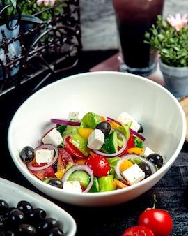 Un plato de ensalada griega con pepino tomate pimiento amarillo cebolla roja aceituna y queso blanco