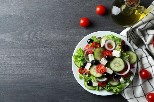 Plato de ensalada griega sobre fondo de madera oscura.