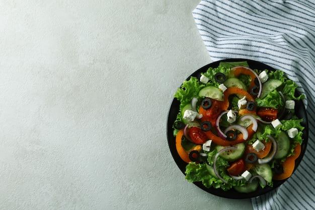 Plato de ensalada griega y toalla de cocina sobre fondo de textura blanca