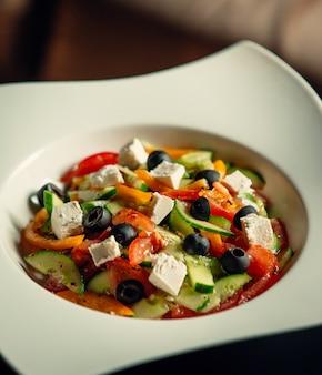 Un plato de ensalada griega con tomate, pepino, queso blanco, aceituna