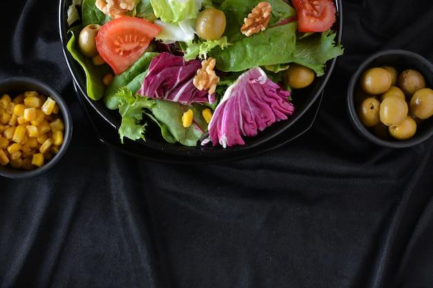 Plato de ensalada con lechuga, tomate, aceitunas y aceite. sobre un paño negro