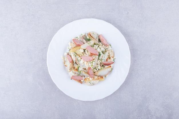 Plato de ensalada con salchichas sobre fondo de piedra.