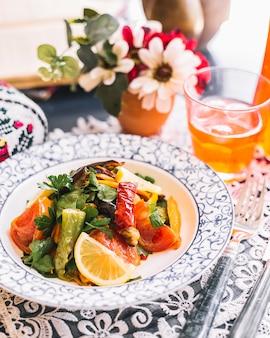 Un plato de ensalada de vegetales salteados con pimientos berenjena tomate hierbas y limón