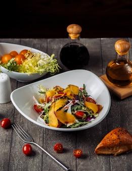 Un plato de ensalada de verduras gresh servido con salsa de granada y aceite.