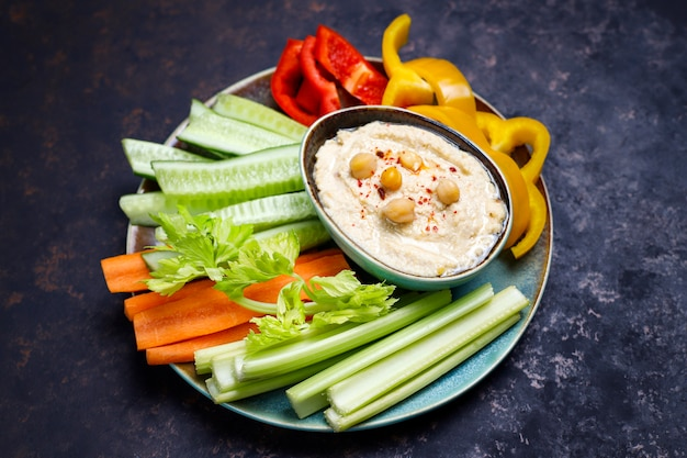 Plato de ensalada de verduras orgánicas frescas con hummus sobre una superficie de hormigón o marrón oscuro