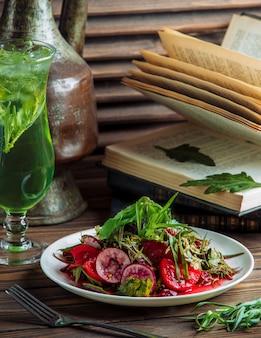 Un plato de ensalada de verduras con un vaso de jugo verde.