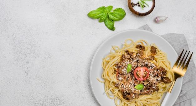 Plato con espagueti a la boloñesa con cubiertos y espacio de copia