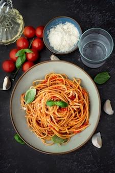 Un plato de espagueti y pasta ingredientes sobre fondo negro