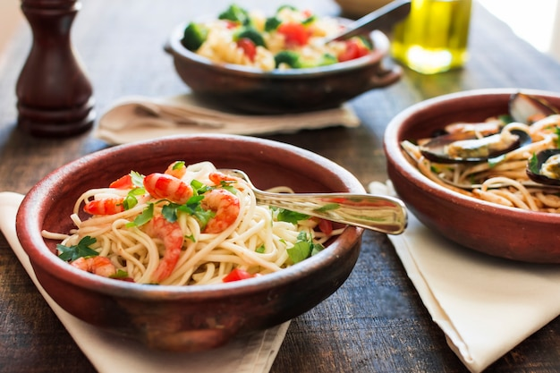 Plato de espaguetis con camarones en mesa de madera
