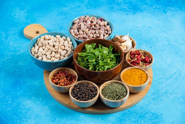 Plato de especias y frijoles crudos sobre fondo azul.