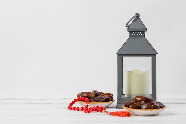 Plato de fechas jugosas con cuentas de oración rojas y una vela en un soporte de linterna sobre fondo blanco