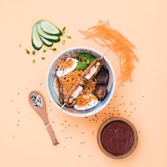 Plato de fideos con verduras; huevos; ensalada y salsa sobre fondo coloreado.