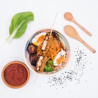 Plato de fideos con verduras y huevos con salsa; semillas de sésamo y cuchara de madera sobre fondo blanco