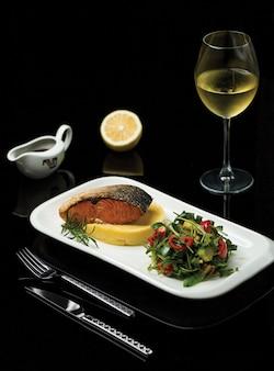 Un plato de filete de salmón a la parrilla con especias y ensalada verde servido con una copa de vino italiano
