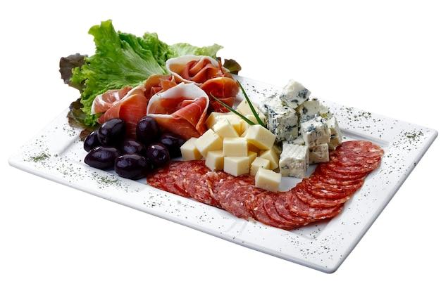 Plato frío con queso, pepperoni, aceitunas y ensalada sobre fondo blanco aislado