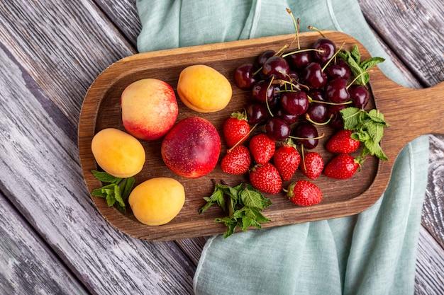 Plato de fruta saludable, fresas, manzanas, duraznos, albaricoques en una mesa de madera gris oscuro, vista superior, primer plano, enfoque selectivo.
