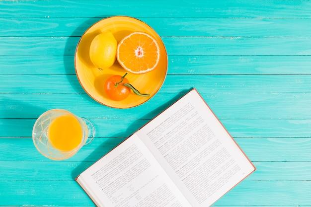 Plato de fruta, vaso de zumo y libro sobre mesa.
