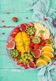 Plato de frutas y bayas. mango, kiwi, higo, fresa, uva, pera y naranja. cocina vegana. menú dietético .