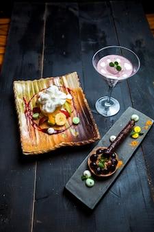 Plato de frutas con crema, tartaleta de chocolate y crema de arándanos