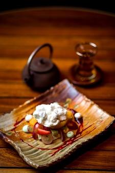 Plato de frutas cubierto con crema y azúcar en polvo