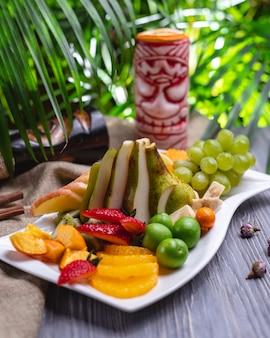 Plato de frutas mandarina fresa cereza ciruela plátano uva melocotón kiwi vista lateral