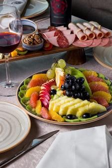 Plato de frutas con pomelo naranja kiwi uva piña manzana roja y verde